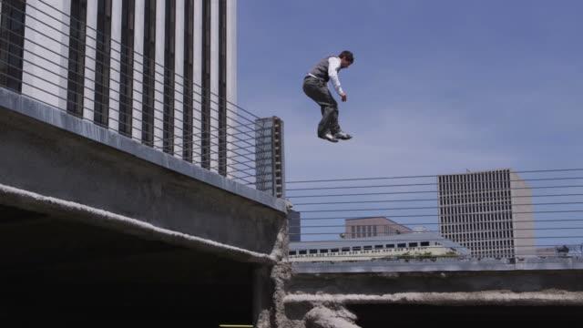 geschäftsmann springen über hürden parkgarage - stuntman stock-videos und b-roll-filmmaterial