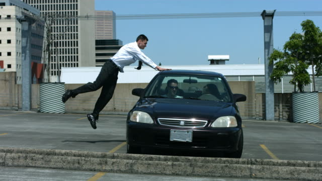 Businessman jumps over car in parking lot, slow motion video