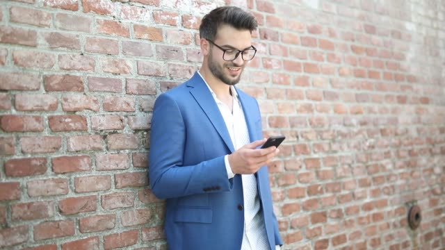 businessman leaning on a brick wall, texting on his phone, smiling and being surprised