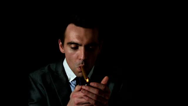 stockvideo's en b-roll-footage met businessman lighting his cigar on black background - overhemd en stropdas