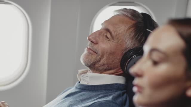 ジェット機でヘッドフォンで音楽を聴くビジネスマン - 乗客点の映像素材/bロール