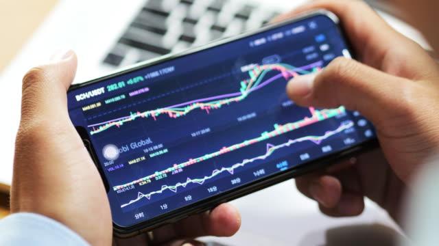 vidéos et rushes de homme d'affaires regarder l'information stock sur le téléphone intelligent - investissement