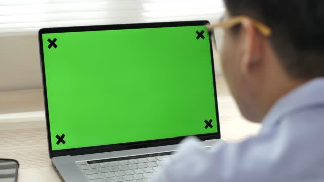 Businessman looking at green screen computer