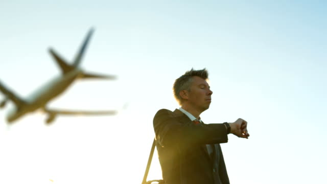 businessman looking at his watch as a passenger plane flies overhead - business travel stock videos and b-roll footage