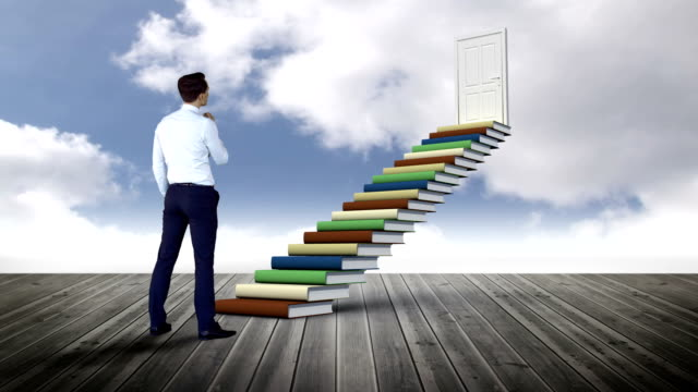 Businessman looking at stair made of books on a wood ground