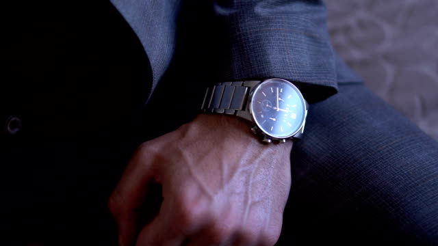 vídeos de stock e filmes b-roll de businessman looking at the time on his wrist watch - watch
