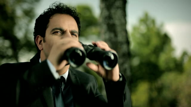 Businessman looking away using binocular in nature. video