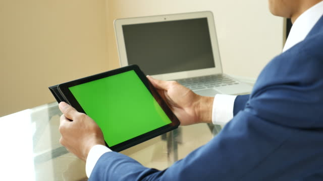 businessman looking on digital tablet with green screen - touchpad video stock e b–roll