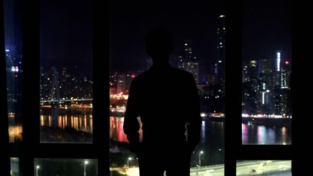 affärsman som tittar ut ur fönstret på natten - titta genom fönster bildbanksvideor och videomaterial från bakom kulisserna