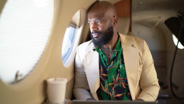 uomo d'affari che guarda attraverso la finestra del jet aziendale - guardare il paesaggio video stock e b–roll