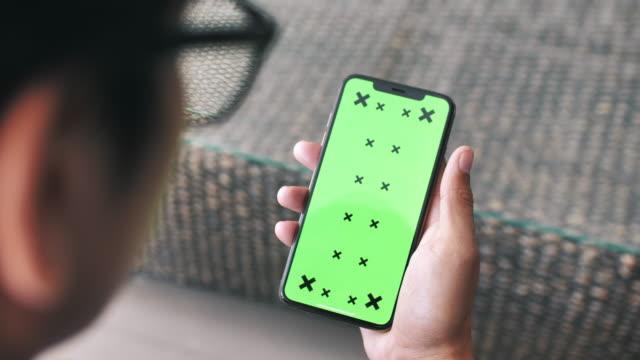 geschäftsmann schaut auf smartphone-greenscreen - computermaus stock-videos und b-roll-filmmaterial
