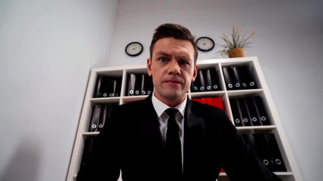 businessman looks thru a magnifying lens and find some interesting in you - оптический инструмент стоковые видео и кадры b-roll