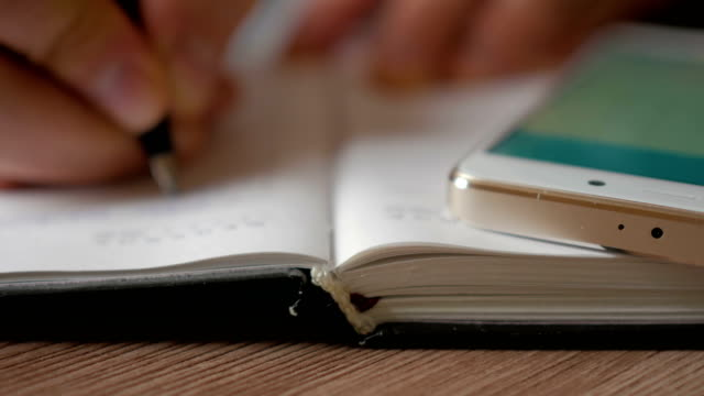 Businessman makes notes in a notebook. Man writes a pen in daily. Smartphone. A person makes notes in the organizer.