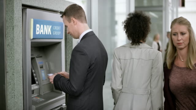 businessman making a withdrawal from the atm machine - banks and atms stock videos & royalty-free footage
