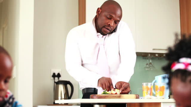 Businessman making breakfast for his children video