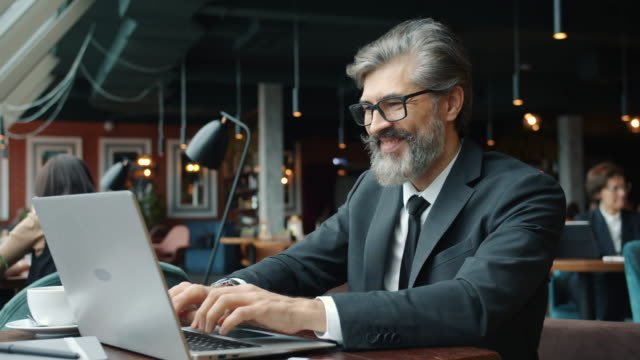 Businessman making online payment using credit card and laptop in cafe showing thumbs-up