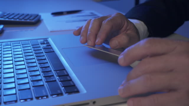 4K DOLLY : businessman making online payment Close up businessman hand making e-commerce payment at night. gold card stock videos & royalty-free footage