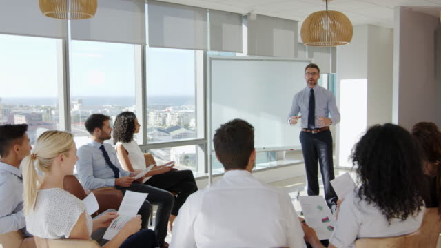 Businessman Making Presentation To Colleagues In Office Businessman Making Presentation To Colleagues In Office presentation stock videos & royalty-free footage