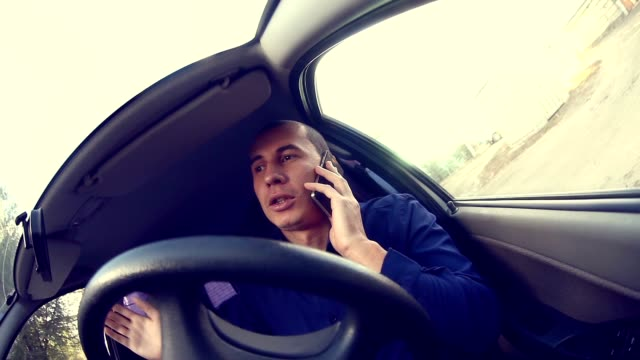 businessman man manager in the car talking on the phone talks conviction video