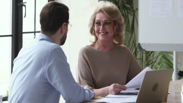 Businessman manager consulting happy old businesswoman customer explain contract benefits Businessman sales manager consulting happy old adult mature senior businesswoman customer client hr explain insurance contract deal benefits selling services at office business meeting job interview salesman stock videos & royalty-free footage