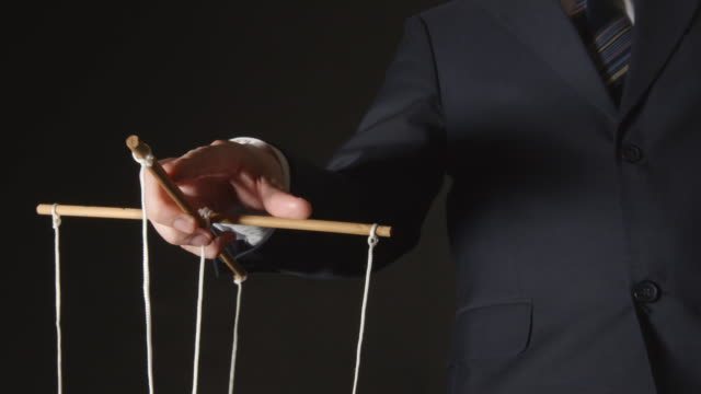 MANIPULATION: Businessman manipulating MANIPULATION: Businessman manipulating marionette stock videos & royalty-free footage