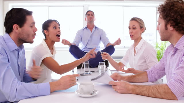 Businessman meditating while his colleagues are arguing video