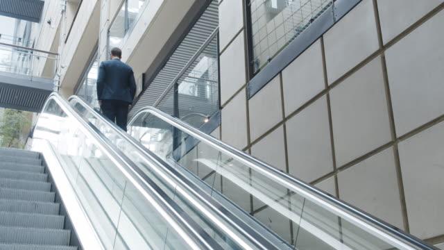 vídeos de stock, filmes e b-roll de empresário subindo na escada rolante - escada rolante