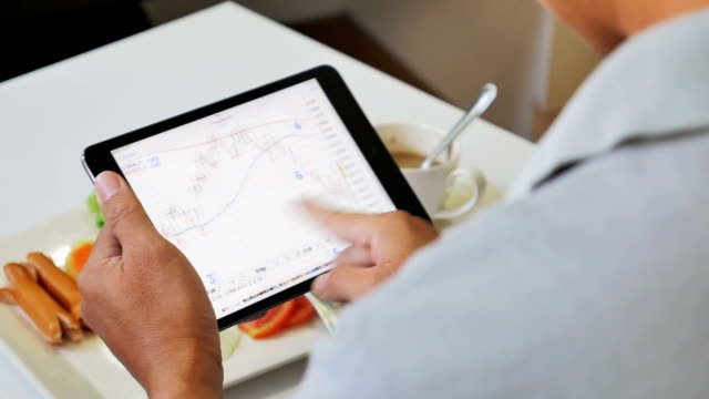 Businessman nalyzing market data information on a digital tablet video
