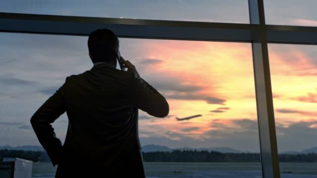 stockvideo's en b-roll-footage met zakenman observeren van het vliegtuig opstijgen door de glazen muur op de luchthaven tijdens het gesprek op de telefoon - vliegveld vertrekhal