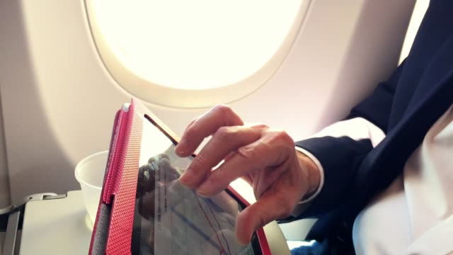 businessman on a passenger plane working with his tablet pc businessman on a passenger plane working with his tablet pc military private stock videos & royalty-free footage
