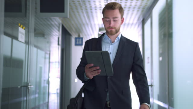 Empresário sobre seu tablet digital no corredor - vídeo