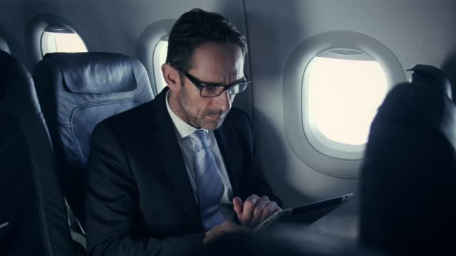 businessman on plane - business travel stock videos and b-roll footage