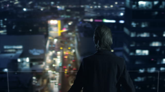 Businessman on the Roof is Looking at Night City