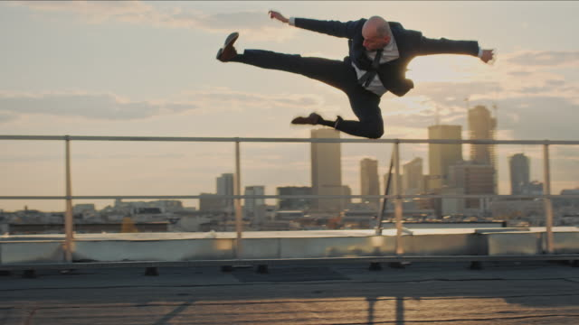 Businessman on the rooftop. Crazy jump