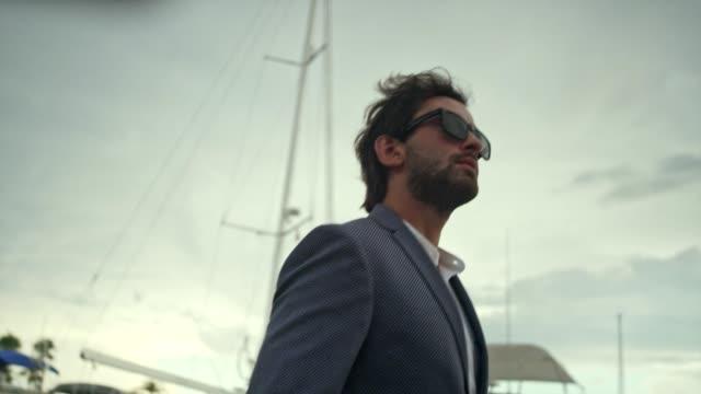 vídeos de stock e filmes b-roll de businessman on vacation. walking on marina - abundância