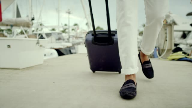 Businessman on vacation. Walking with suitcase on marina Escaping from work. Businessman on vacation yachting stock videos & royalty-free footage