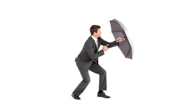 Businessman opening umbrella and struggling video