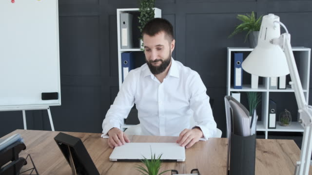 Businessman packing his belongings in carton box after finishing video call