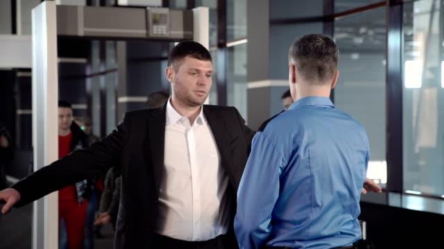 affärsman som passerar gränskontrollen med metalldetektor - vakta bildbanksvideor och videomaterial från bakom kulisserna