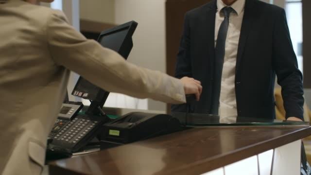 biznesmen płacąc kartą kredytową w hotelu - credit card filmów i materiałów b-roll