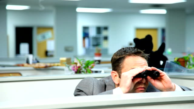 Businessman peeking over cubicle with binoculars