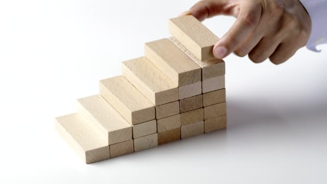 vídeos de stock e filmes b-roll de businessman placing last wooden block to complete staircase, show growth and improvement - bloco