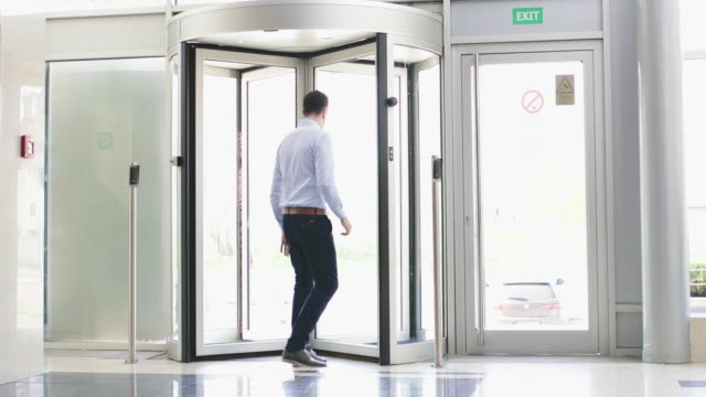 Businessman playing with revolving door video