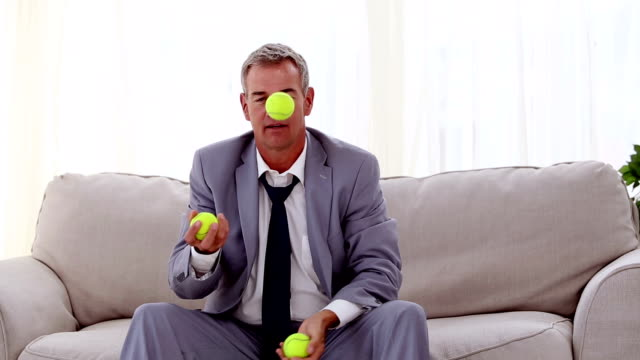 Businessman playing with tennis ball video