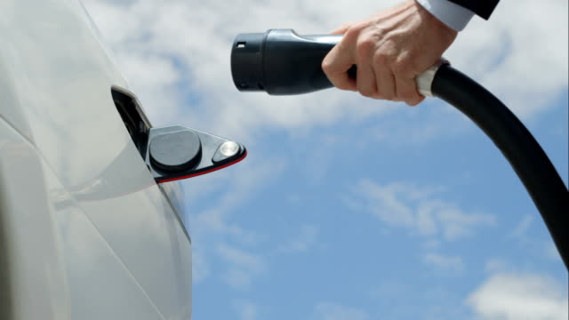 CLOSE UP: Businessman plugging in white electric car at charging station video