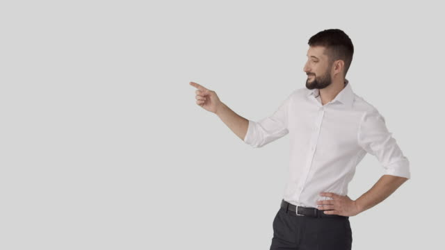 Businessman pointing at white background Confident businessman pointing finger at white background arms akimbo stock videos & royalty-free footage