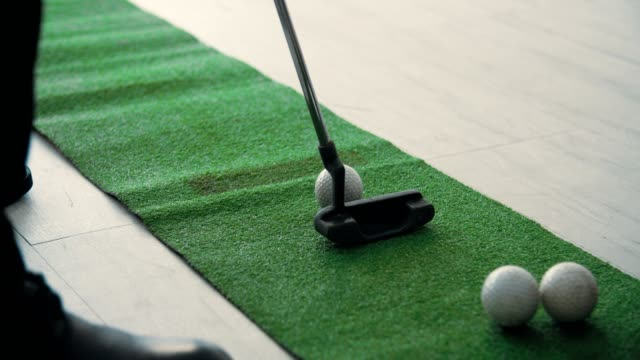 Businessman Practicing Golf Putting in Office
