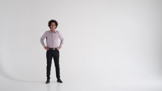 uomo d'affari che presenta sullo sfondo dello studio - mani sui fianchi video stock e b–roll