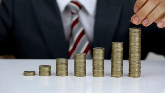 Businessman Protecting And Rising Coins Stack On Desk