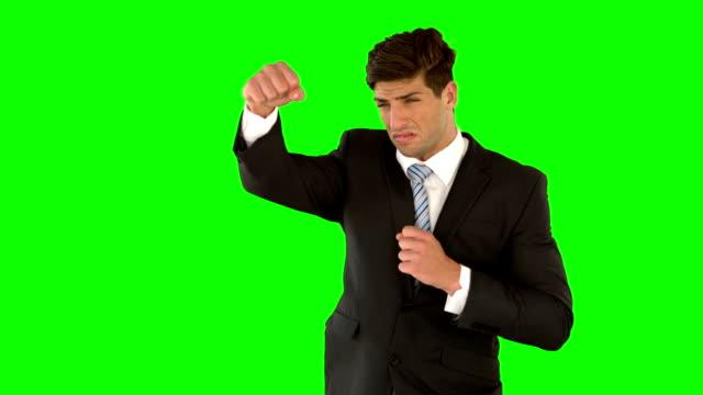 uomo d'affari timbratura su schermo verde - colpire con un pugno video stock e b–roll